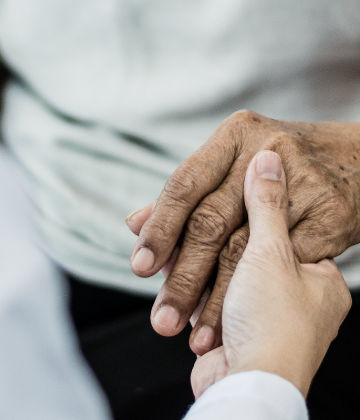 image of a carer holding a person's hand