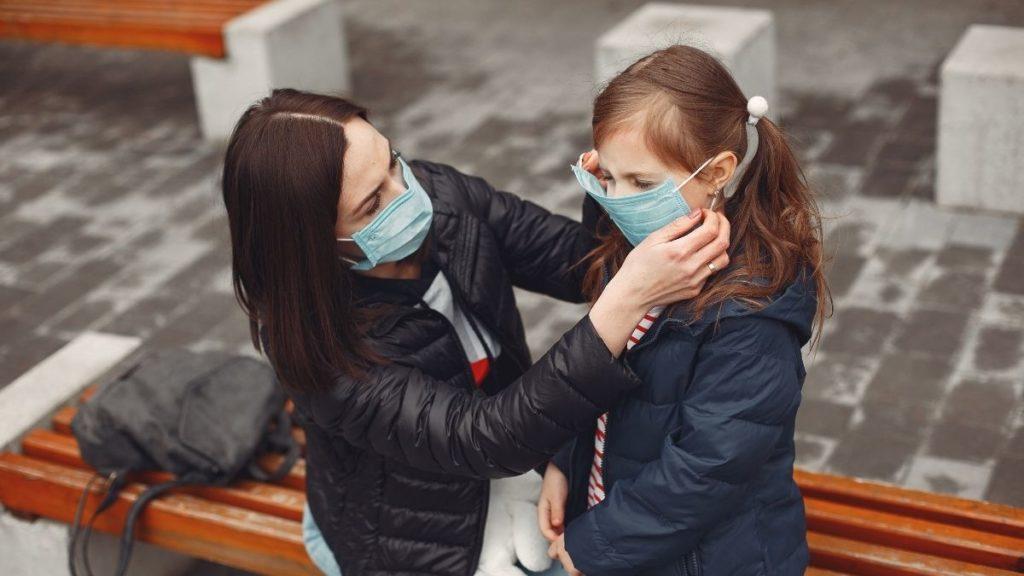 Mother adjusts daughter's mask